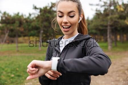 Portrait of a smiling sportswoman in earphones Stock photo © deandrobot