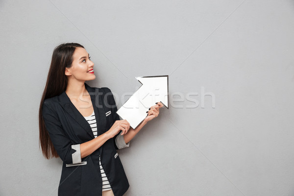 Smiling business woman pointing with paper arrow and looking up Stock photo © deandrobot
