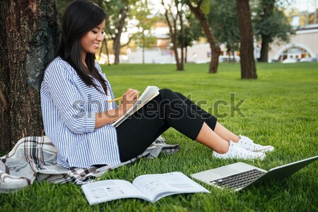 Top view of charming asian female student taking notes, while li Stock photo © deandrobot