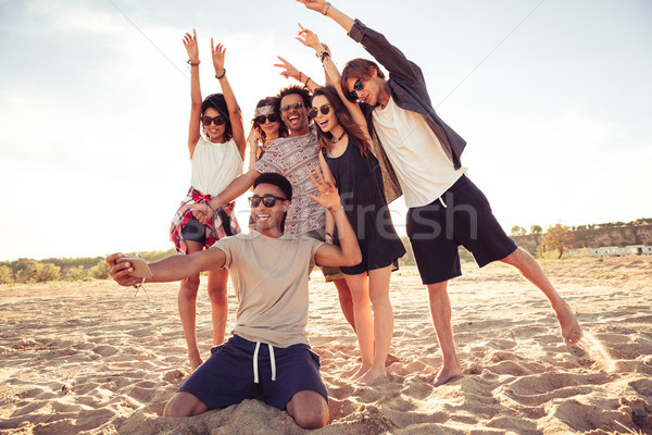 Excited young friends on the beach make selfie Stock photo © deandrobot