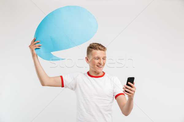 Photo of satisfied hipster boy holding commercial poster copyspa Stock photo © deandrobot
