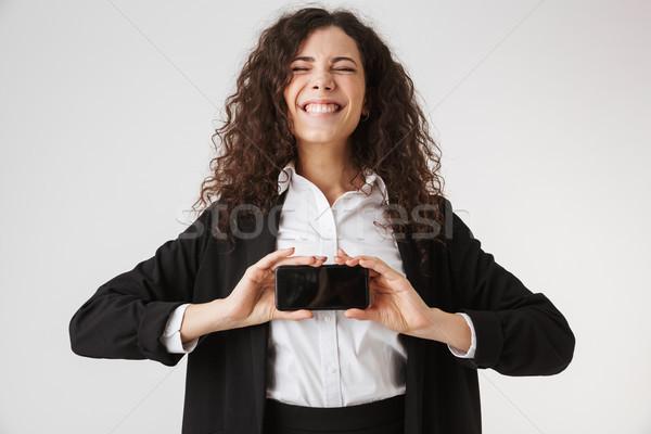 Feliz jovem mulher de negócios exibir telefone móvel Foto stock © deandrobot