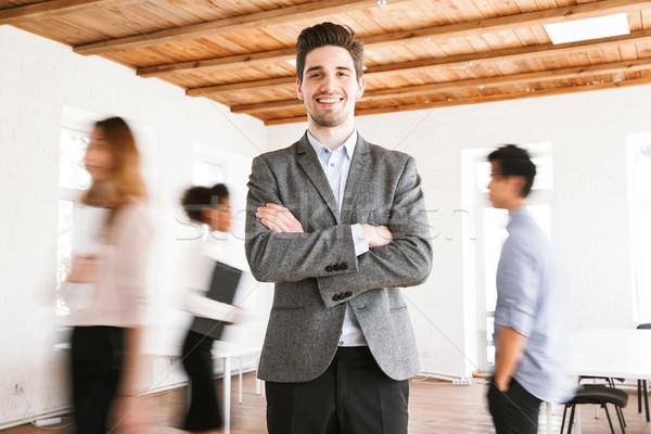 улыбаясь молодые деловой человек Постоянный оружия сложенный Сток-фото © deandrobot