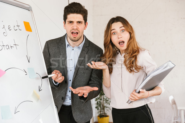 Shocked young business couple presenting a project Stock photo © deandrobot