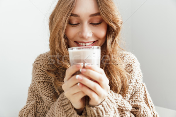 Photo of european attractive woman 20s drinking glass of latte,  Stock photo © deandrobot