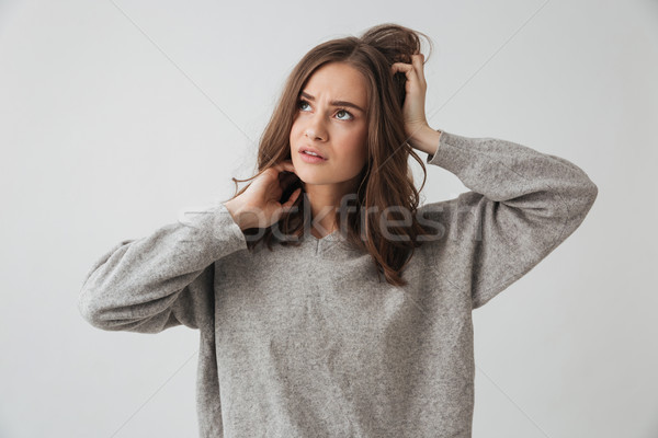 Pensive woman in sweater holding her head and looking up Stock photo © deandrobot