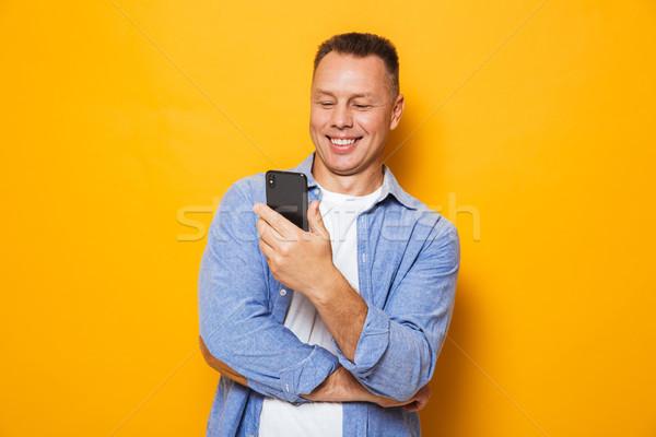 Portré boldog középkorú férfi néz mobiltelefon izolált Stock fotó © deandrobot