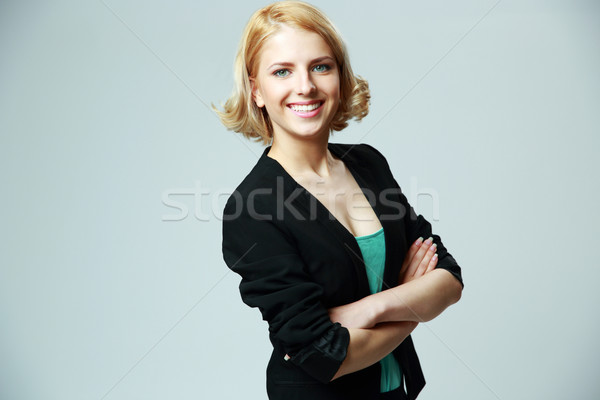 Portrait of a young cheerful woman with arms folded on gray background Stock photo © deandrobot