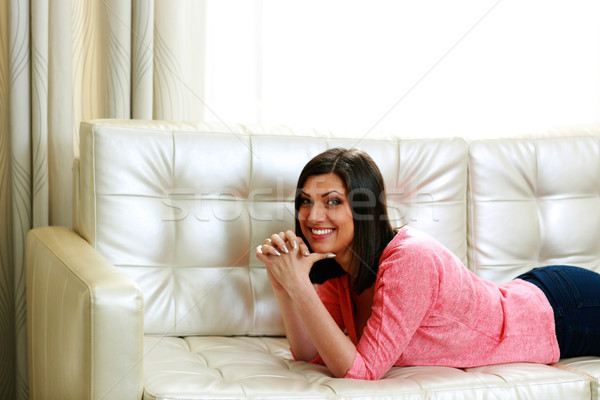 Middle-aged cheerful woman lying on the sofa Stock photo © deandrobot