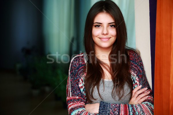Portrait of a cute smiling woman standing with arms folded at home Stock photo © deandrobot