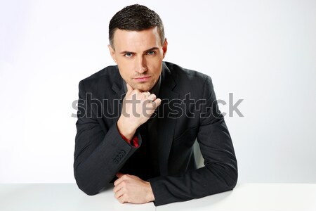 Confident businessman sitting at the table over gray background Stock photo © deandrobot