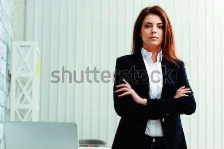 Jóvenes pensativo mujer de negocios pie armas doblado Foto stock © deandrobot