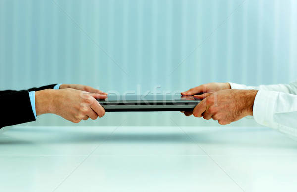 Closeup image of a business hands pulling a laptop. Competition for new vacation. Stock photo © deandrobot