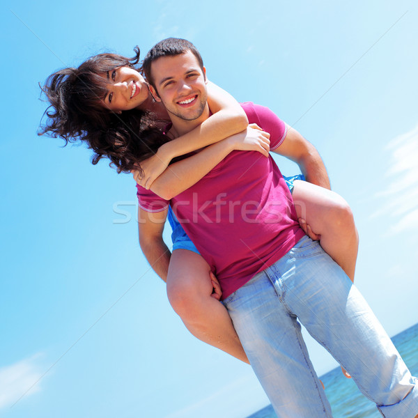 Happy young couple in casual cloths at the beach in sunny weather Stock photo © deandrobot