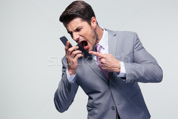 Angry businessman shouting on the phone Stock photo © deandrobot