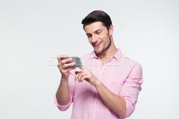 Happy businessman using smartphone Stock photo © deandrobot