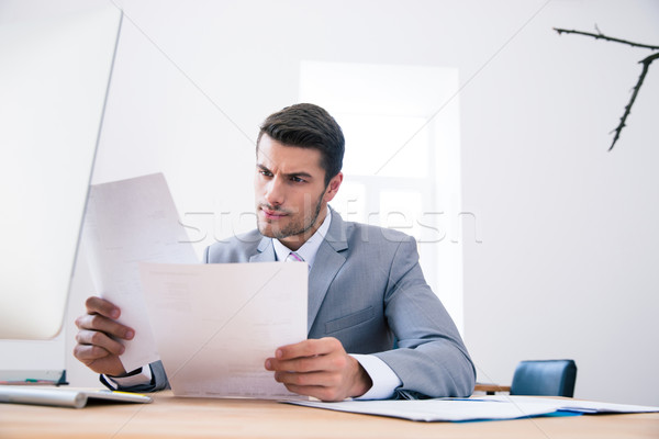 Businessman reading papers in office Stock photo © deandrobot