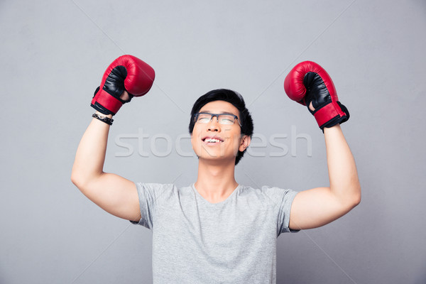 Asian man in boxing gloves rejoices victory Stock photo © deandrobot