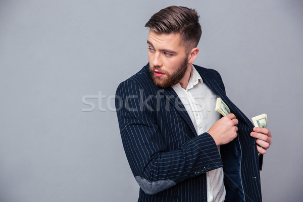 Businessman putting money into jacket Stock photo © deandrobot