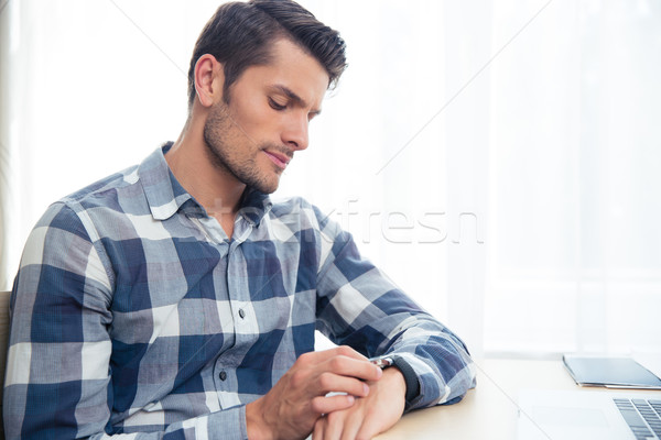 Man looking on wrist watc Stock photo © deandrobot