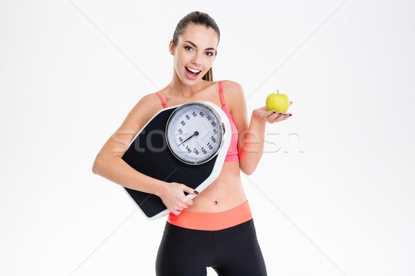 Excited positive fitness girl holding weighing scale and apple Stock photo © deandrobot