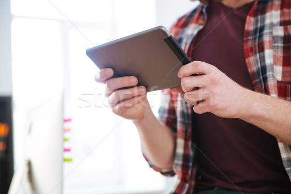 Closeup of tablet used by man in checkered shirt  Stock photo © deandrobot