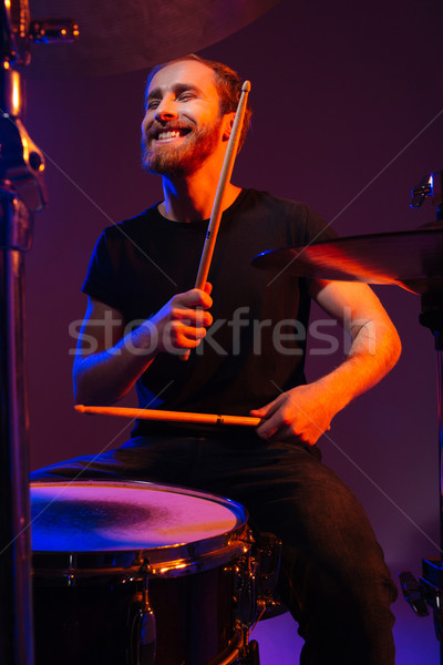 Happy cheerful bearded man drummer playing on kit with sticks Stock photo © deandrobot