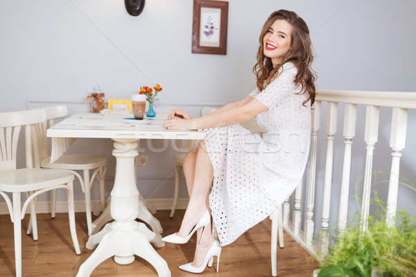 Beautiful young woman in white dress sitting at cafe  Stock photo © deandrobot