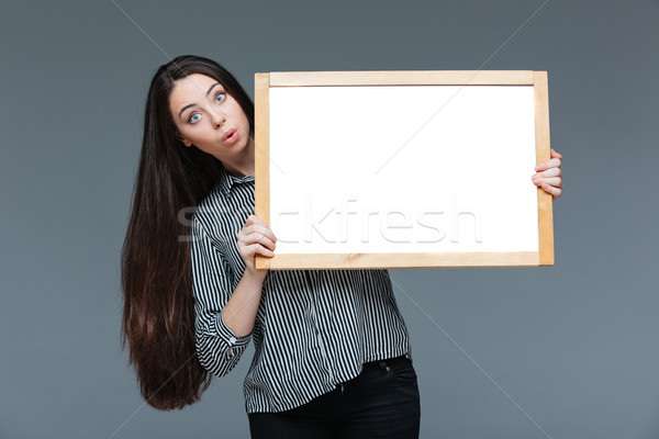 Amazed businesswoman holding blank board Stock photo © deandrobot