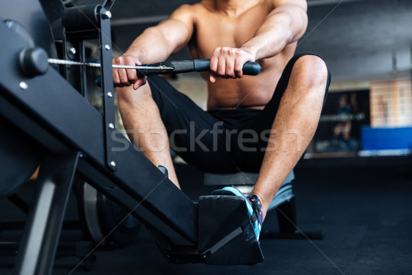 Muscular fitness man using rowing machine  Stock photo © deandrobot