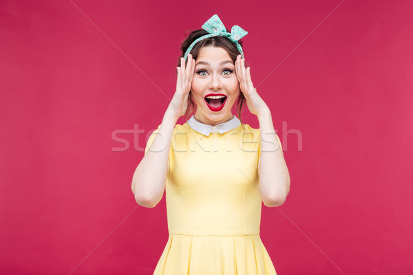 Cheerful beautiful pinup girl with hands touching her face Stock photo © deandrobot