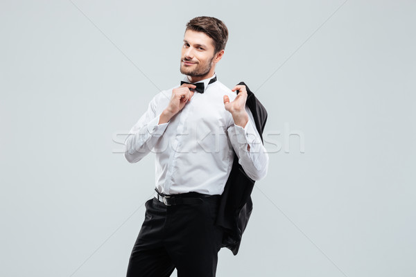 Attractive young man in tuxedo holding his jacket Stock photo © deandrobot