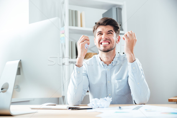 Crazy irritated businessman holding crumpled paper and working on workplace Stock photo © deandrobot