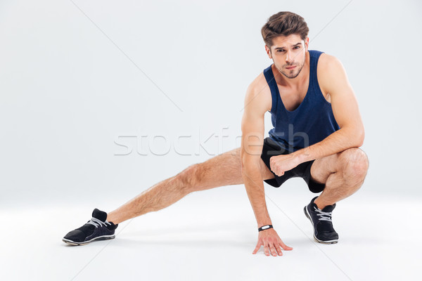 Attractive young male athlete stretching his legs Stock photo © deandrobot