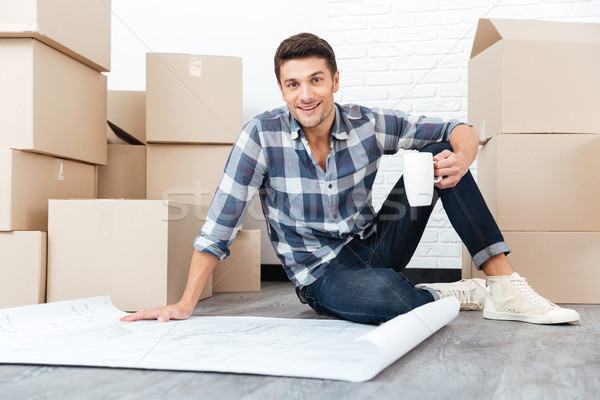 Stock photo: Happy young man looking at house blueprints