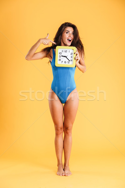 Portrait of woman in swimsuit pointing finger on big clock Stock photo © deandrobot