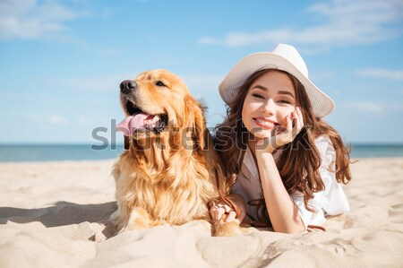 Cheerful young woman sitting and hugging her dog on beach Stock photo © deandrobot