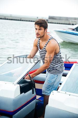 Yakışıklı genç oturma deniz Stok fotoğraf © deandrobot