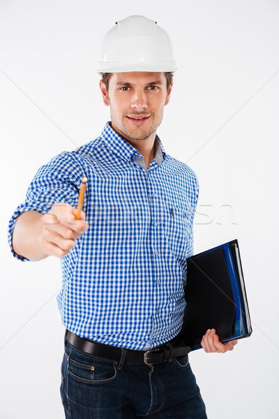 Smiling young man builder in building helmet pointing on you Stock photo © deandrobot