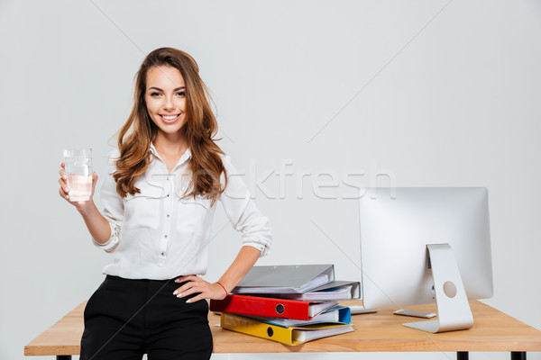 Businesswoman holding glass of water while standing in the office Stock fotó © deandrobot
