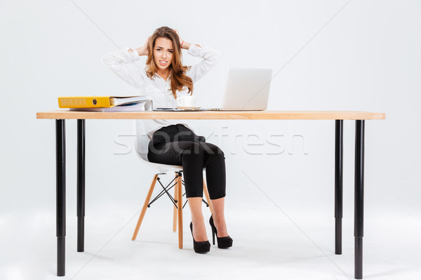 Confused embarrased young businesswoman working with laptop at the table Stock photo © deandrobot