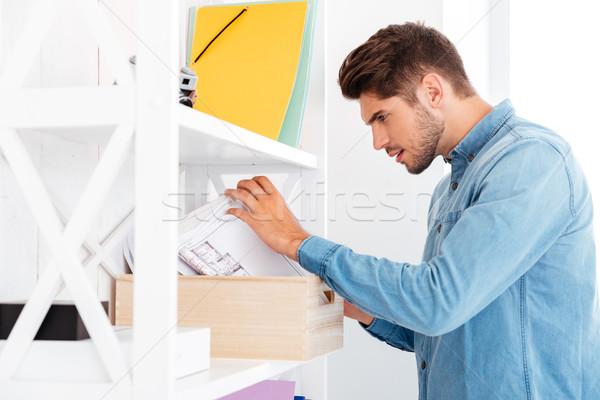 бизнесмен глядя документы служба шельфа красивый Сток-фото © deandrobot