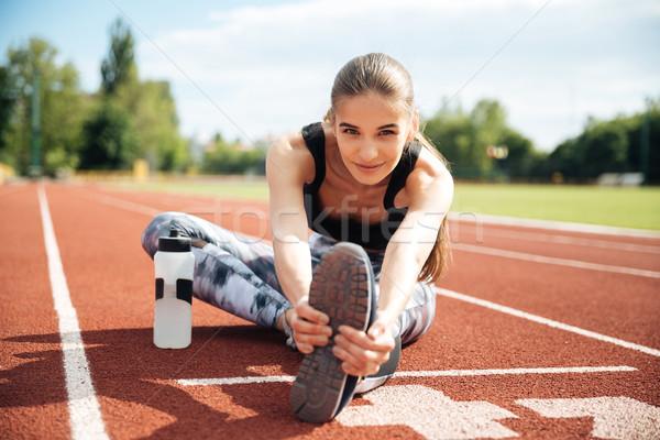 Smiling woman athlete stretching legs on stadium Stock photo © deandrobot