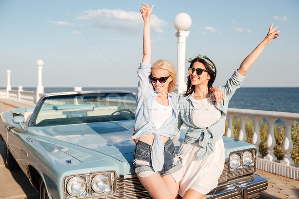 Two women standing with raised hands near vintage cabriolet Stock photo © deandrobot
