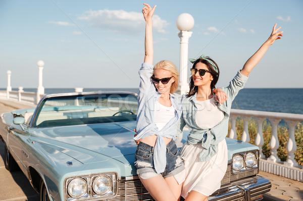 Duas mulheres em pé as mãos levantadas vintage cabriolé dois Foto stock © deandrobot