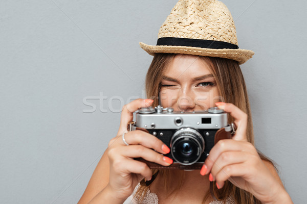Attractive young girl in hat winking and holding camera Stock photo © deandrobot