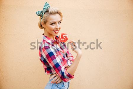 Smiling cute pin up girl cover her eye with lollipop Stock photo © deandrobot