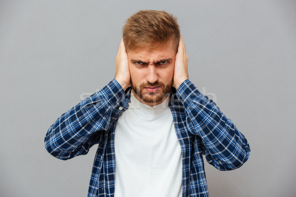 Angry annoyed bearded man covering ears with palms Stock photo © deandrobot