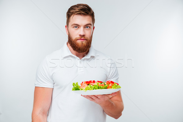Portrait of a bearded man holing plate with fresh salad Stock photo © deandrobot