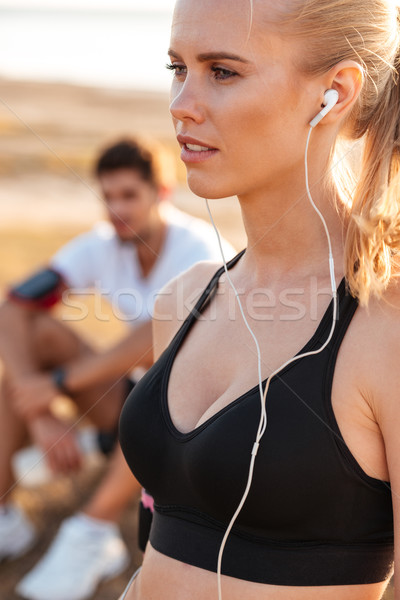 Beautiful young blonde sports woman with earphones Stock photo © deandrobot